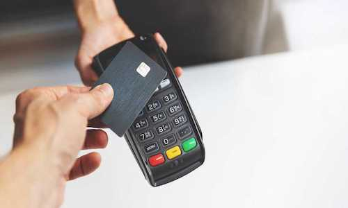 A credit card being tapped on a transaction device.
